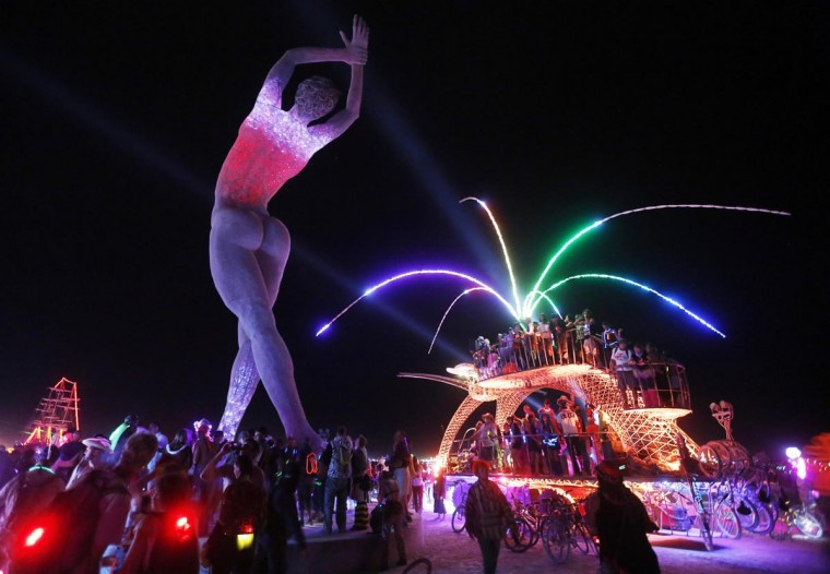 "Participants dance around and atop an art car parked beside the ""Truth is Beauty"" sculpture created by Marco Cochrane at the 2013 Burning Man arts and music festival in the Black Rock desert of Nevada, August 30, 2013. (Jim Bourg/Reuters)"