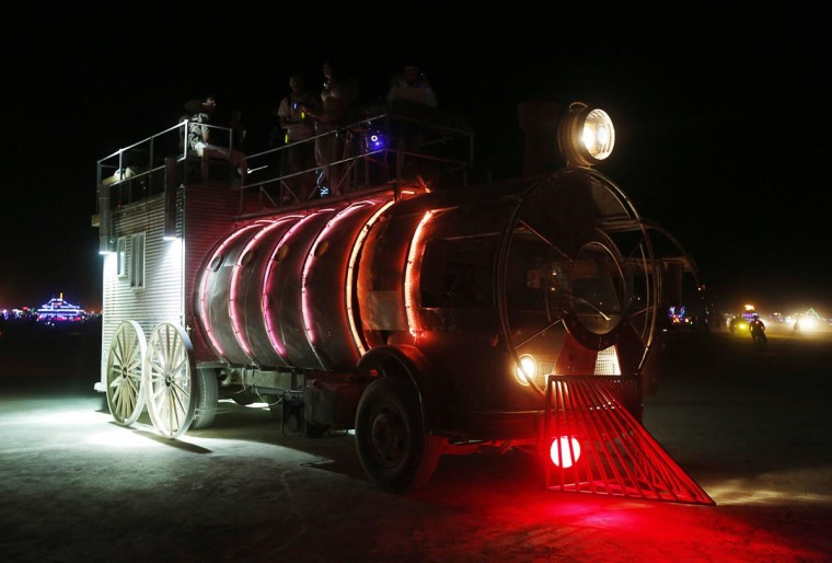 An art car shaped like a train drives across the desert in the early morning hours at the 2013 Burning Man arts and music festival in the Black Rock desert of Nevada, August 30, 2013. (Jim Bourg/Reuters)