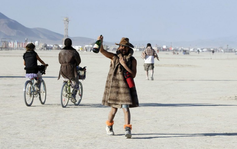 A Burning Man participant toasts the sunrise with a bottle of champagne at the 2013 Burning Man arts and music festival in the Black Rock desert of Nevada, August 30, 2013. (Jim Bourg/Reuters)