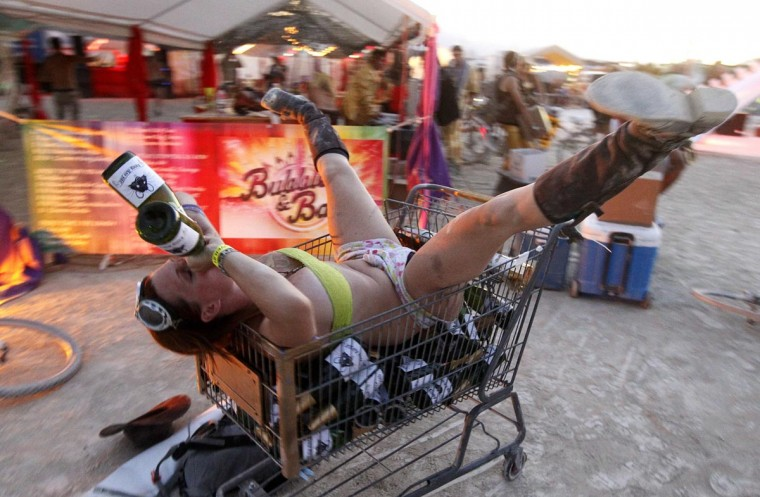 "A participant who goes by the playa name ""Honey B"" drinks from bottles of champagne as she lies atop empty bottles in a shopping cart during the ""Gold Bikini Happy Hour"" hosted by Rat Camp at the 2013 Burning Man arts and music festival in the Black Rock desert of Nevada, August 30, 2013. (Jim Bourg/Reuters)"
