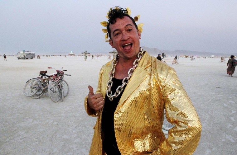 "Burning Man participant Fritz Gomez Wood gives a thumbs up during the ""Gold Bikini Happy Hour"" hosted by Rat Camp at the 2013 Burning Man arts and music festival in the Black Rock desert of Nevada, August 30, 2013. (Jim Bourg/Reuters)"