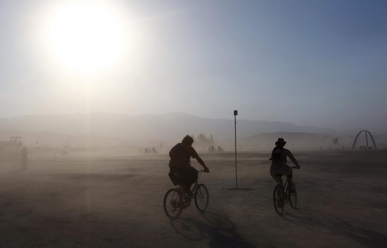 Two Burning Man participants cycle through a dust storm at the 2013 Burning Man arts and music festival in the Black Rock desert of Nevada, August 30, 2013. (Jim Bourg/Reuters)