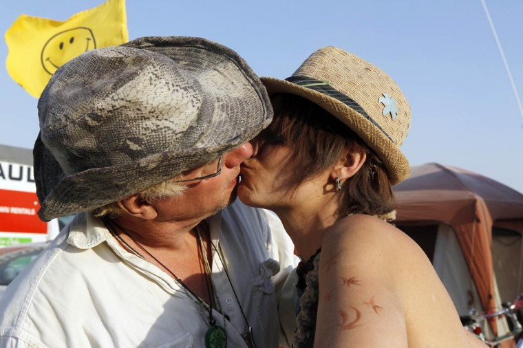 "Two Burning Man participants who go by the playa names ""Gogo"" (L) and ""Poptart"" kiss at the 2013 Burning Man arts and music festival in the Black Rock desert of Nevada, August 30, 2013. (Jim Bourg/Reuters)"