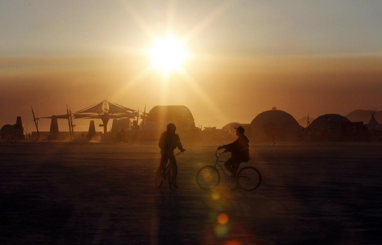 Burning Man participants bike across the desert at sunrise at the 2013 Burning Man arts and music festival in the Black Rock desert of Nevada, August 30, 2013. (Jim Bourg/Reuters)