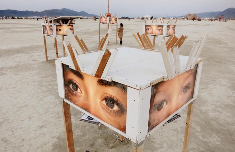 A participant looks at art works on the playa at sunrise, during the 2013 Burning Man arts and music festival in the Black Rock desert of Nevada, August 29, 2013. (Jim Bourg/Reuters)