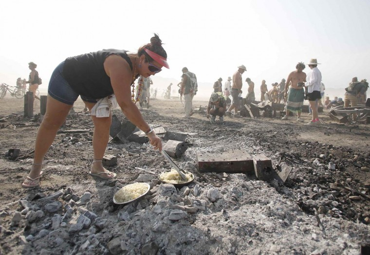 Rhonda Clark cooks hash browns for breakfast on the burned remains of the Man during the Burning Man 2013 arts and music festival in the Black Rock Desert of Nevada, September 1, 2013. (Jim Urquhart/Reuters)
