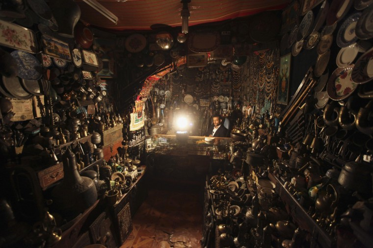 An antiques seller waits by a lantern for customers in his shop during a blackout in Sanaa. Large parts of Yemen, including the capital Sanaa, have been left without electricity after Yemeni tribesmen attacked power lines a Yemeni official said. (Mohamed al-Sayaghi/Reuters photo)