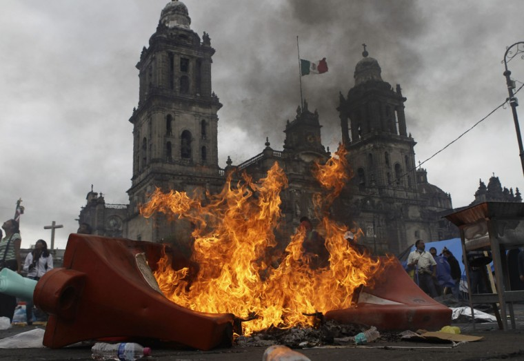 Members of the teachers' union CNTE and protesters stand near a burning barricade before they are evicted from Zocalo Square by the riot police in downtown Mexico City. (Henry Romero / Reuters)