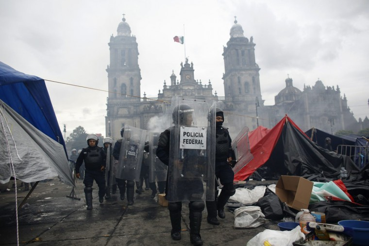 Riot policemen walk in front of the cathedral on the Zocalo after dispersing demonstrators in Mexico City. (Tomas Bravo / Reuters)