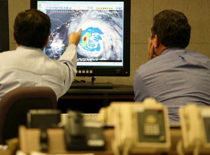 Hurricane forecaster James Franklin (L) and Dr. Richard Pasch discuss Hurricane Isabel at the National Hurricane Center in Miami, Florida, September 17, 2003. Isabel was on a path that would bring it ashore on September 18 on the North Carolina coast, then north along the Chesapeake Bay near Washington D.C., through Virginia, Maryland and Pennsylvania, the U.S. National Hurricane Center said. (Marc Serota/Reuters photo)