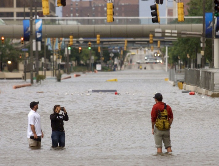 People wade down flooded Pratt Street in downtown Baltimore, Maryland taking pictures of each other September 19, 2003, as water due to Hurricane Isabel overflowed from Baltimore Harbor onto several streets of the downtown area overnight. 13 people are dead and 4.5 million people are without power from the Carolinas to New York. (Joe Giza/Reuters photo)