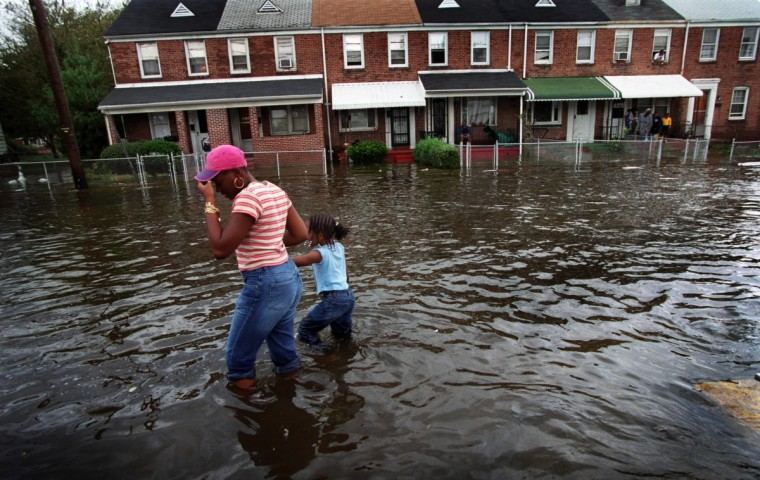 Crystal Pulley and daughter Brianna, 6,wade through knee-deep water, the remnants of Hurricane Isabel, on Sollers in the Turner's Station area Friday, September 19, 2003. (Glenn Fawcett/Baltimore Sun)