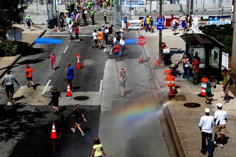 A woman stands near a spraying fire hydrant at the Grand Prix of Baltimore. (Kaitlin Newman/Baltimore Sun)