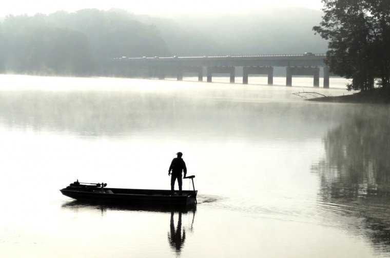 A fisherman heads out for a day of fishing on Liberty Reservoir in the early morning fog. In the background is Route 26, Liberty Road, overpass. (Robert K. Hamilton/Baltimore Sun)