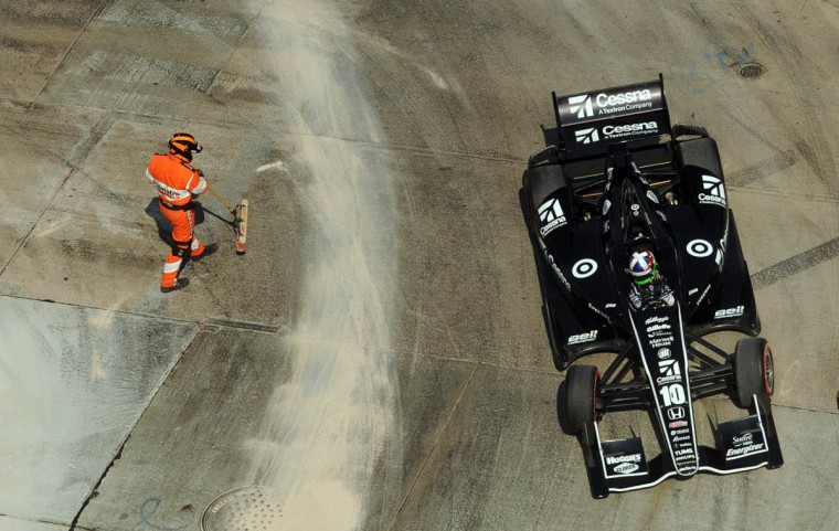 As Dario Franchitti drives by turn #3, a safety official cleans up a spill left by Luca Filippi when his car started smoking after racing past turn #3. (Algerina Perna/ Baltimore Sun)
