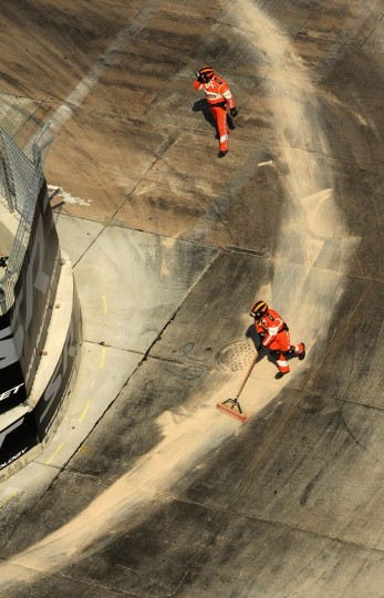 Track personnel clean up a spill from Luca Filippi's (#98) race car at turn #3. (Algerina Perna/Baltimore Sun)