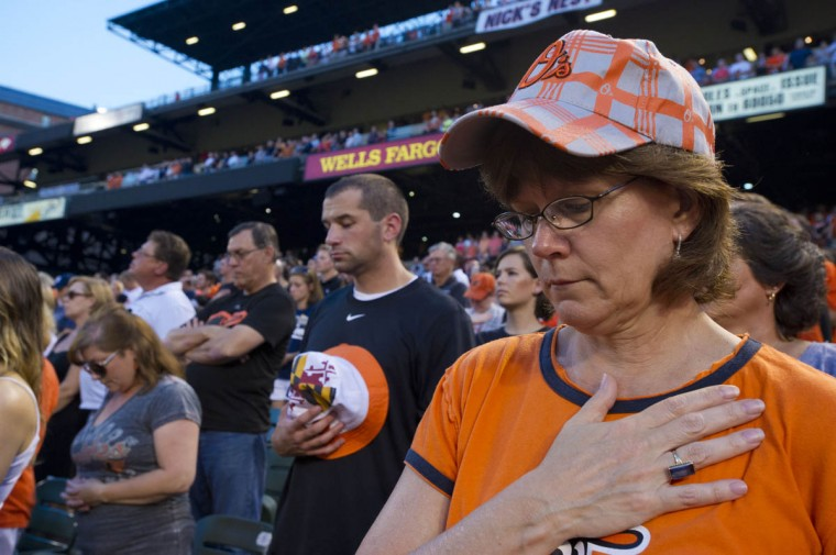 Pam Offutt of Reisterstown holds her hand over her heart during a moment of silence in remembrance of the 12th anniversary of the 9/11 attacks during pregame at Oriole Park at Camden Yards Wednesday, Sep. 11, 2013. (Karl Merton Ferron/Baltimore Sun)