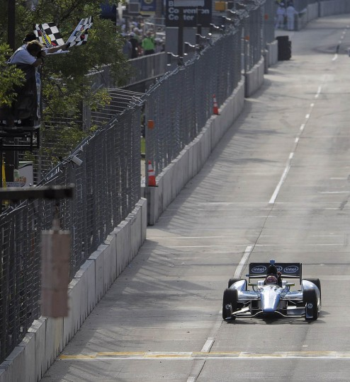 Simon Pagenaud drives beneath the checkered flag during the IZOD IndyCar Series at the 2013 Grand Prix of Baltimore. Simon Pagenaud captured the flag. (Karl Merton Ferron/Baltimore Sun)