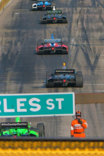 A member of the track safety crew stands by as Indy cars avoid the scene where Scott Dixon's Target car was disabled on the main straightaway near Charles Street during the IZOD IndyCar Series at the 2013 Grand Prix of Baltimore. Simon Pagenaud captured the flag. (Karl Merton Ferron/Baltimore Sun)