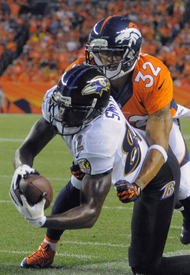 Baltimore Ravens wide receiver Torrey Smith (82) comes down with a first down reception in front of Denver Broncos cornerback Tony Carter (32) setting up a touchdown Thursday, Sep. 5, 2013. Baltimore Ravens vs. Denver Broncos NFL football at Mile High Stadium. (Karl Ferron/Baltimore Sun)