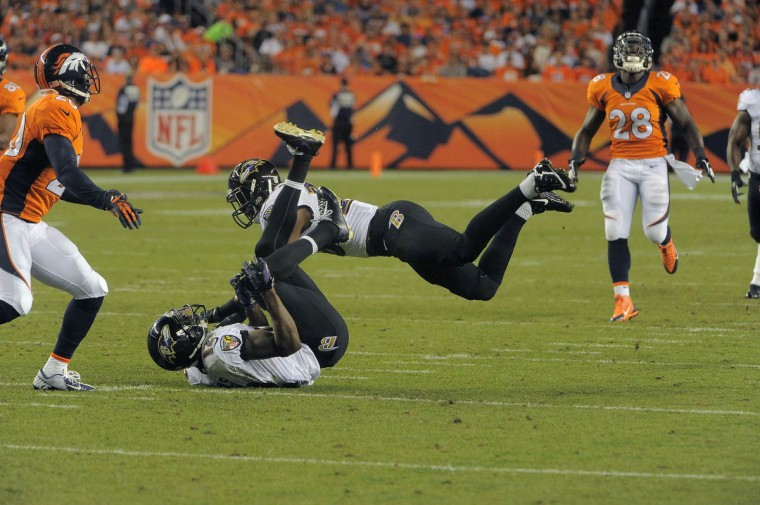 Baltimore Ravens' Jacoby Jones (12) is throttled by safety Brynden Trawick during a kick to Denver Thursday, Sep. 5, 2013. Baltimore Ravens vs. Denver Broncos NFL football at Mile High Stadium. (Karl Ferron/Baltimore Sun)