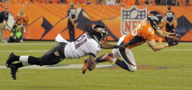 Broncos #83 Wes Welker makes a third quarter catch as Ravens' #21 Lardarius Webb makes the tackle. Baltimore Ravens vs. Denver Broncos NFL football at Mile High Stadium. (Karl Merton Ferron/Baltimore Sun)