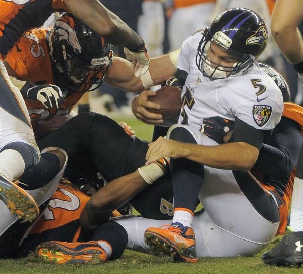 A host of Denver Broncos pile onto Baltimore Ravens quarterback Joe Flacco (5) for a sack during the third quarter at Mile High Stadium. (Karl Merton Ferron/Baltimore Sun)