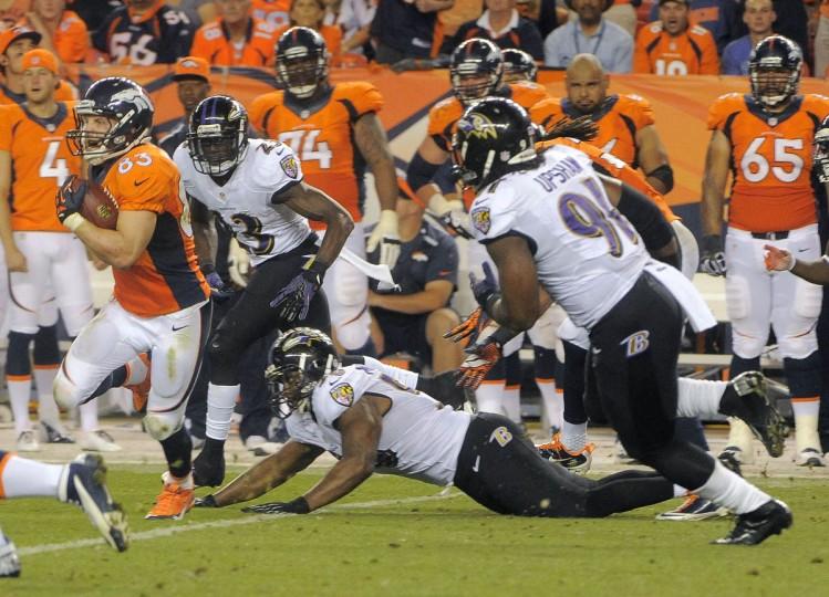Denver Broncos wide receiver Wes Welker (83) runs past Baltimore Ravens cornerback Chykie Brown (23), linebacker Albert McClellan and outside linebacker Courtney Upshaw (91) during the fourth quarter at Mile High Stadium. (Karl Merton Ferron/Baltimore Sun)