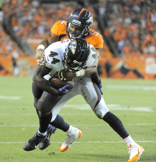Ravens' #44 Vonta Leach scores a first quarter touchdown as Broncos #52 Wesley Woodyard makes a late tackle. Baltimore Ravens vs Denver Broncos NFL football at Sports Authority Field at Mile High Stadium. (Lloyd Fox/Baltimore Sun)