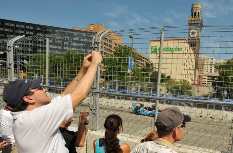 Fans capture the action of the Grand Prix IZOD IndyCar Series Warm-up on Pratt Street through the fencing. (Amy Davis /Baltimore Sun)