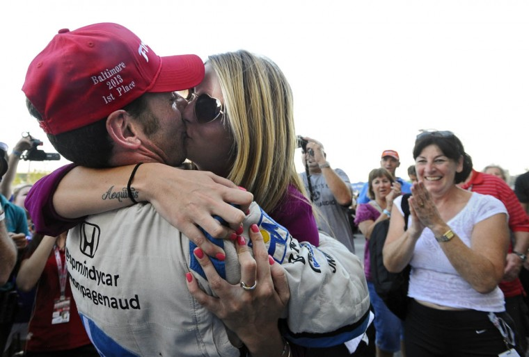 Simon Pagenaud, left, winner of the 2013 Grand Prix of Baltimore, celebrate with a kiss from girl friend Hailey McDermott as Pagenaud's mother Sylvie, right, looks on at pit lane. (Kenneth K. Lam/Baltimore Sun)