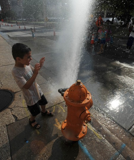 Christopher DiJulio (5) of Arnold, finds relief from the heat at the Grand Prix of Baltimore via a hydrant with a sprinkler attachment. (Jerry Jackson/Baltimore Sun)