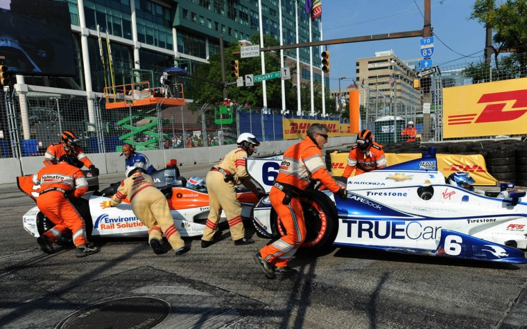 Safety crew members work to clear a seven car tangle in turn one on lap 57 during the 2013 Grand Prix of Baltimore (Jerry Jackson/Baltimore Sun)