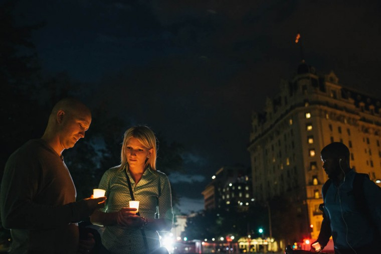 Dave Gray and wife Brittany, of Salt Lake City, hold candles in remembrance of people affected by gun violence during a vigil at Freedom Plaza on September 16, 2013 in Washington, DC. The vigil, during which organizers called for stricter gun laws, was in remembrance of the 12 victims killed in a shooting at the Washington Navy Yard earlier in the day. (Greg Kahn/Getty Images)
