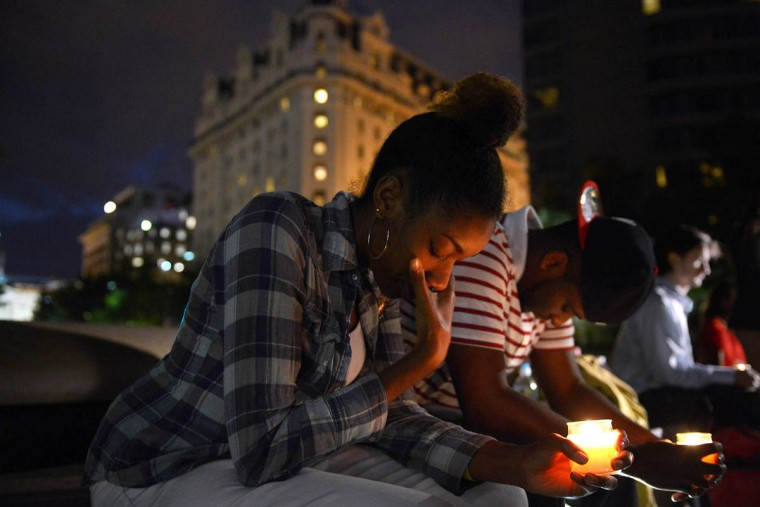 Brittany Carter, center, and Jibri Johnson, right center, take part in a candlelight vigil Monday night at Freedom Plaza in Washington. A gunman at the Navy Yard military complex in Washington killed at least 12. (Matt McClain/Washington Post))