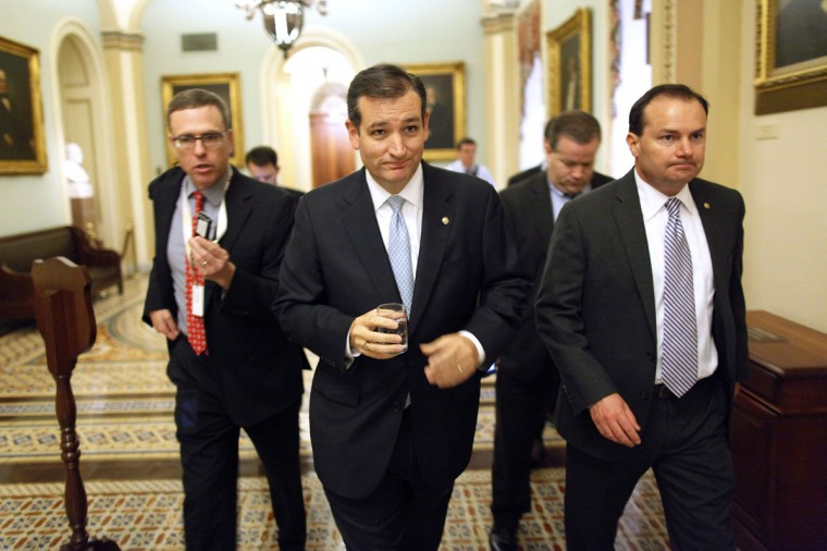 U.S. Senator Ted Cruz (R-TX) (C) and Senator Mike Lee (R-UT) (R) depart the Senate floor after their speeches before the night-time budget vote at the U.S. Capitol in Washington, October 16, 2013. The U.S. Senate, racing to avert a government default, on Wednesday passed legislation raising the Treasury Department's borrowing authority and sent the measure to the House of Representatives for final passage. REUTERS/Jonathan Ernst