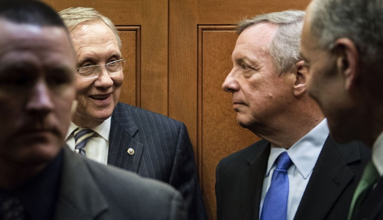 Senate Majority Leader Senator Harry Reid (D-NV) (2L) smiles toward Senate Democratic Whip Senator Richard Durbin (D-IL) (2R) and Senator Charles E. Schumer (D-NY) (R) in an elevator after a vote on Capitol Hill October 16, 2013 in Washington, DC. The US Senate passed legislation to compromise on budget and debt concerns to reopen the US federal government funding it to mid January address the debt limit till early February.