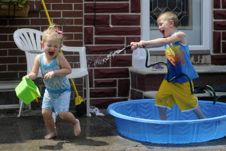 Cousins John Benges, 4, and Karrah Walker, 2, of Baltimore, cool off in a kiddie pool on Cooksie street in Locust Point in June of 2010. (Barbara Haddock Taylor/Baltimore Sun)