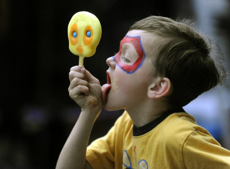 Five year old Burke Marsiglia of Sparks, his face painted like a Superhero, licks the drips from a Tweety Bird ice cream pop at the Federal Hill Jazz and Blues Festival in June 2010. (Barbara Haddock Taylor/Baltimore Sun)