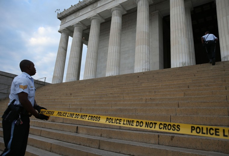 A U.S. Park Police officer uses police tape to close the Lincoln Memorial, October 1, 2013 in Washington, DC. The National Mall and all monuments and large sections of the government will close due to government shut down after Congress failed to agree on spending. (Mark Wilson/Getty Images)