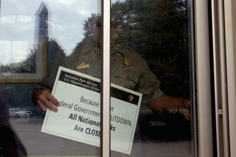 U.S. Park Service employee puts a closed sign in the window of the World War II Memorial ticket office on the National Mall October 1, 2013 in Washington, DC. National Park Service park facilities and grounds were closed and more than 21,000 of the service's employees were furloughed after Congress was unable to agree on a federal budget and shut down for the first time in 17 years. ( Chip Somodevilla/Getty Images)