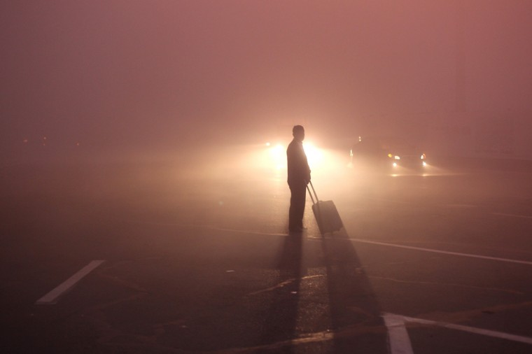 A man waits for taxi in front of Changchun Railway Station as heavy smog engulfs the city on October 22, 2013 in Changchun, China. Expressways, schools and an airport remain closed as heavy smog continues to disrupt northeast China. (ChinaFotoPress via Getty Images)