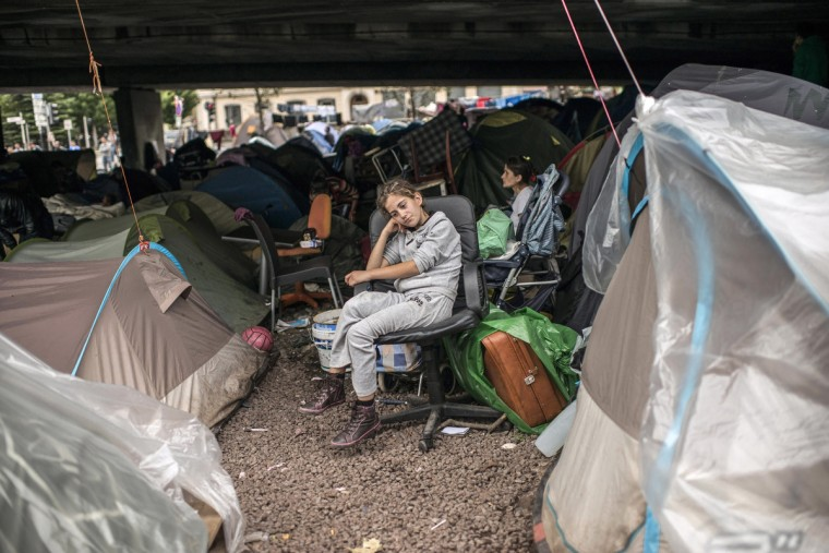 A young woman sits near tents in an illegal campsite of Albanian asylum seekers, situated under the A6 motorway's Kitchener bridge next to the entrance of the Fourviere tunnel in Lyon, France. A court today ordered the immediate expulsion of the camp of 300 people, including 98 children, who have been camping beneath the highway bridge since July. The interior ministry also said today that it would seek an overhaul of the asylum system. (Alexander Roth-Grisard/Getty Images)