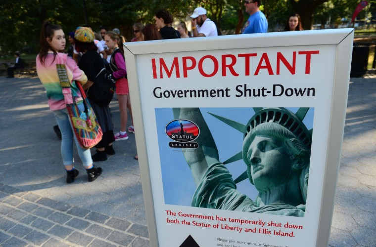 Tourists walk by a sign announcing that the Statue of Liberty is closed due to a US government shutdown in New York, October 1, 2013. Government institutions and national parks around the US were closed and thousands of employees were furloughed after Congress was unable to agree on a federal budget and shut down the government for the first time in 17 years. (Emmanuel Dunand/Getty images)