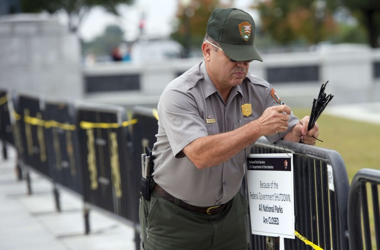 US Park Ranger Richard Trott places a closed sign on a barricade in front of the World War II monument in Washington, DC, October 1, 2013. (Jim Watson/Getty images)