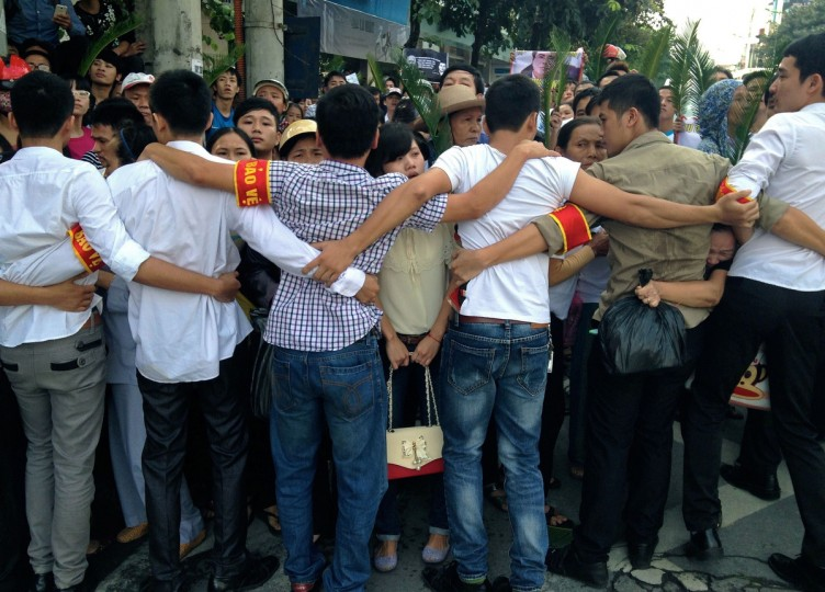 Vietnamese plainclothes policemen form a human chain to prevent hundreds of protestors from approaching the People's Court where Vietnamese activist lawyer Le Quoc Quan faces charges of tax evasion at his trial held amid heavy security in Hanoi. Police shut roads and used human chains to stop hundreds of protestors from attending the trial of Vietnamese Catholic lawyer Le Quoc Quan, who has been in detention since December 2012 when he blogged on a range of sensitive topics prior to his arrest including civil rights, political pluralism and religious freedom. (Cat Barton/Getty Images)