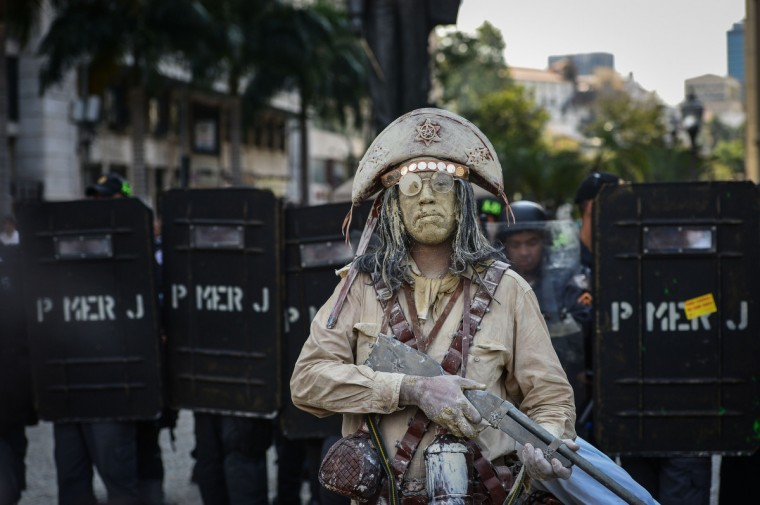 A street performer is seen during a teacher protest against corruption in the office of Rio Governor Sergio Cabral, in Rio de Janeiro, Brazil. Brazil has seen large street protests since last June, directed towards the country's ruling elite in demand of better public services and an end to political corruption. (Yasuyoshi Chiba/Getty Images)
