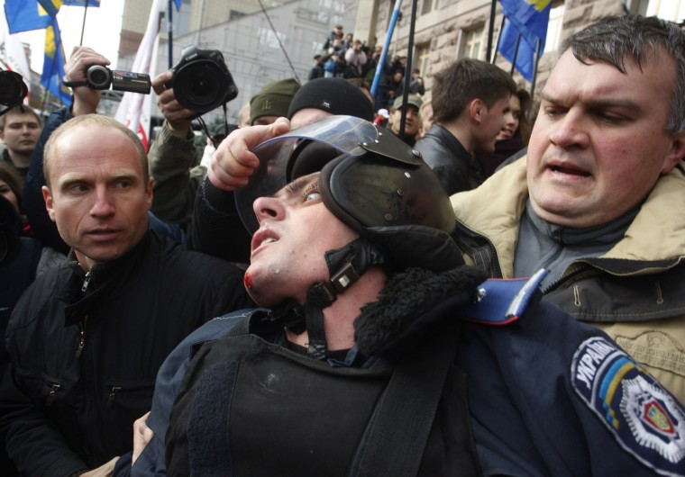 Ukrainian opposition activists grabs the helmet of a riot policeman as they try to enter the building of Kiev's city council to prevent a session in Kiev. Several hundred of people rallied at the Kiev city administration trying to break the city council session and demand to hold council elections. The credentials of the city's deputies ended on July 2, 2013, and the opposition insists that their session is illegal. (Yury Kirnichny/Getty Images)