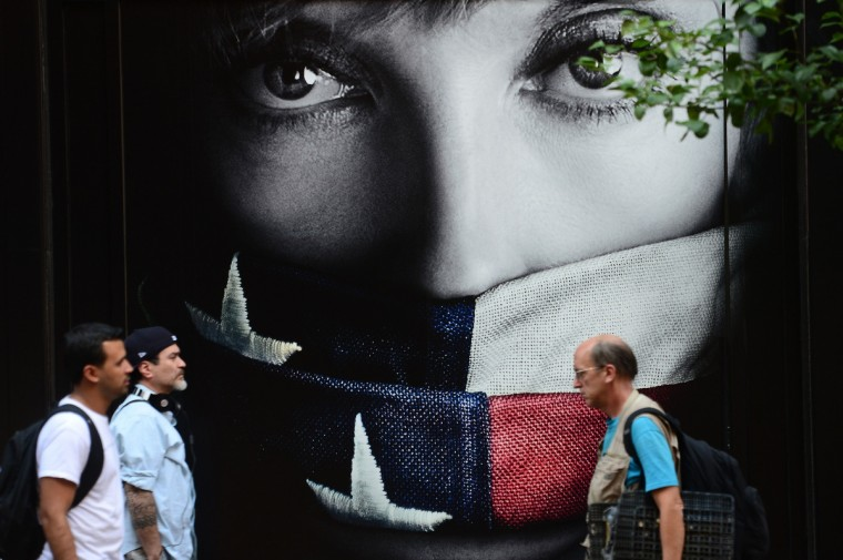 People walk by a television series advertisement featuring actress Toni Colette gagged by a US flag in New York on. Government institutions and national parks around the US were closed and thousands of employees were furloughed after Congress was unable to agree on a federal budget and shut down the govermment for the first time in 17 years. (/Emmanuel Dunand/Getty images)