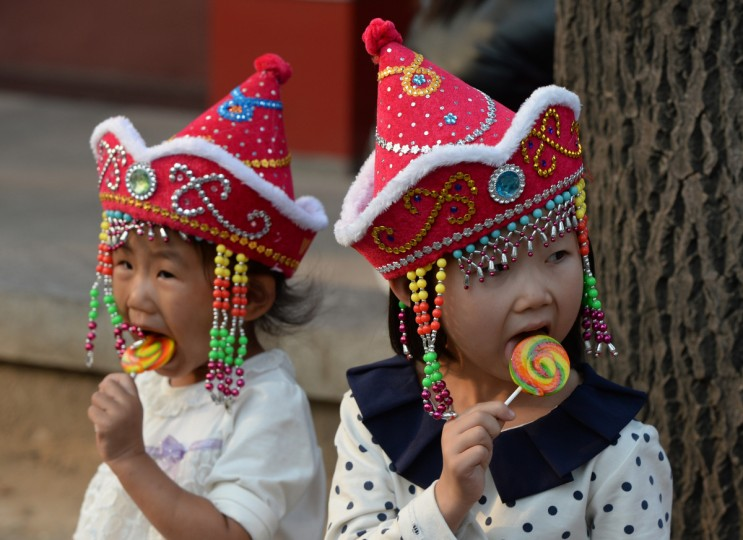 Young Chinese tourists eat lollipops during their visit to Tiananmen Square in Beijing. Chinese tourists should not pick their noses in public, pee in pools or steal airplane life jackets, China's image-conscious authorities have warned in a handbook in their latest effort to counter unruly behavour. (Mark Ralston/Getty images)